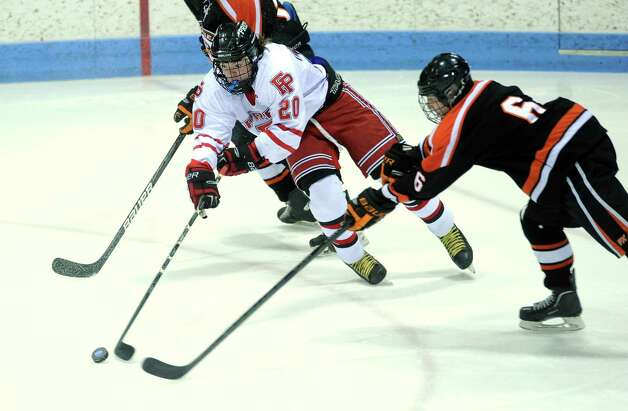 Fairfield Prep's Tim Edmonds controls the puck as Ridgefield's Liam Smith defends during the boys hockey State Tournament Class I Semifinals Wednesday, Mar. 13, 2013 at Ingalls Rink in New Haven, Conn. Photo: Autumn Driscoll / Connecticut Post