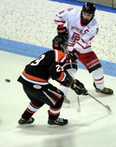 Fairfield Prep's David White passes the puck as Ridgefield's Geoffrey Schneider defends during the boys hockey State Tournament Class I Semifinals Wednesday, Mar. 13, 2013 at Ingalls Rink in New Haven, Conn. Photo: Autumn Driscoll / Connecticut Post
