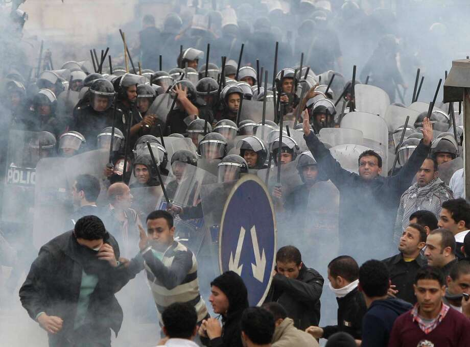 FILE - In this Jan. 28, 2011 file photo, Egyptian anti-government activists clash with riot police in Cairo, Egypt. A government inquiry into the deaths of nearly 900 protesters during Egypt's uprising has concluded police were behind nearly all the killings and used snipers on rooftops overlooking Tahrir Square to shoot into the huge crowds. The report, parts of which were obtained by The Associated Press, is the most authoritative account of the killings and determines the deadly force used could only have been authorized by ousted President Hosni Mubarak's security chief, with the president's full knowledge. (AP Photo/Ben Curtis, File) Photo: Ben Curtis