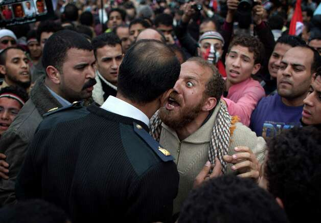 FILE - In this Sunday, Feb. 13, 2011 file photo, an Egyptian protester, center right, argues with a police officer in Tahrir Square in downtown Cairo, Egypt. A government inquiry into the deaths of nearly 900 protesters during Egypt's uprising has concluded police were behind nearly all the killings and used snipers on rooftops overlooking Tahrir Square to shoot into the huge crowds. The report, parts of which were obtained by The Associated Press, is the most authoritative account of the killings and determines the deadly force used could only have been authorized by ousted President Hosni Mubarak's security chief, with the president's full knowledge. (AP Photo/Emilio Morenatti, File) Photo: Emilio Morenatti