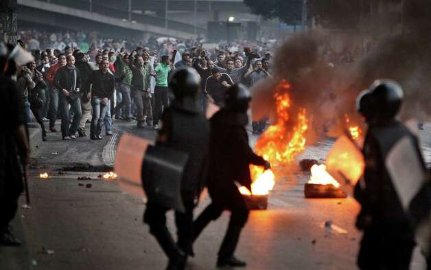 FILE - In this Jan. 26, 2011 file photo, Egyptian riot police clash with anti-government activists in Cairo, Egypt. A government inquiry into the deaths of nearly 900 protesters during Egypt's uprising has concluded police were behind nearly all the killings and used snipers on rooftops overlooking Tahrir Square to shoot into the huge crowds. The report, parts of which were obtained by The Associated Press, is the most authoritative account of the killings and determines the deadly force used could only have been authorized by ousted President Hosni Mubarak's security chief, with the president's full knowledge. (AP Photo/Ben Curtis, File) Photo: Ben Curtis