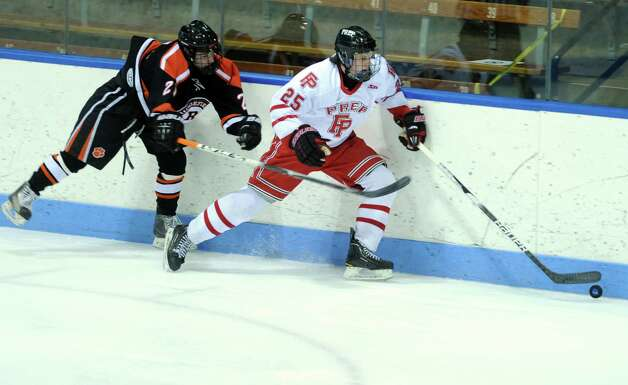 Fairfield Prep's Michael Ventricelli controls the puck as Ridgefield's Cameron McGuire defends during the boys hockey State Tournament Class I Semifinals Wednesday, Mar. 13, 2013 at Ingalls Rink in New Haven, Conn. Photo: Autumn Driscoll / Connecticut Post