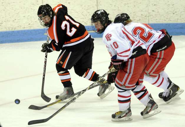 Ridgefield's Cameron McGuire (21) passes the puck as Fairfield Prep's Connor Henry (10) defends during the boys hockey State Tournament Class I Semifinals Wednesday, Mar. 13, 2013 at Ingalls Rink in New Haven, Conn. Photo: Autumn Driscoll / Connecticut Post