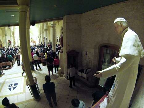 A statue of Pope John Paul II, who visited San Fernando Cathedral in 1987, seems to watch over a Mass at the cathedral on Wednesday, March 13, 2013, to celebrate the naming of Jorge Mario Bergoglio of Argentina as the new Pope Francis I. Photo: Billy Calzada, San Antonio Express-News / San Antonio Express-News