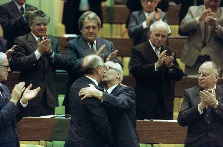 "Now for the kisses that made every politician in the world reconsider, at least for a moment, every kiss they'd ever given another politician. Here Soviet leader Mikhail Gorbachev embraces Erich Honecker, the hardline communist and general secretary of the Communist Party (SED), as East German Prime Minister Willy Stoph (left) looks on, and members of SED applaud during the 11th SED party's congress in 1986 in East Berlin. Honecker ruled East Germany between 1971 and 1989, when he was dismissed as a consequence of the anti-communist revolution.  Stoph was East German premier between 1964 and 1973 and again between 1976 and 1989. He resigned Nov. 7, 1989, two days before the Berlin Wall was broken down. This picture was later referred to as ""the kiss of death."" Photo: WIESELES, Getty / 2012 AFP"