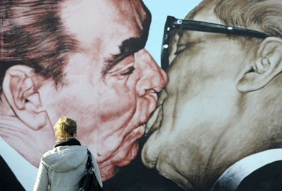 A woman looks at a painting on the so-called East Side Gallery featuring the famous kiss between then-Soviet leader Leonid Brezhnev (left) and East German leader Erich Honecker by Russian artist Dmitry Vrubel in Berlin on Oct. 20, 2009.  Photo: JOHN MACDOUGALL, Getty / 2009 AFP