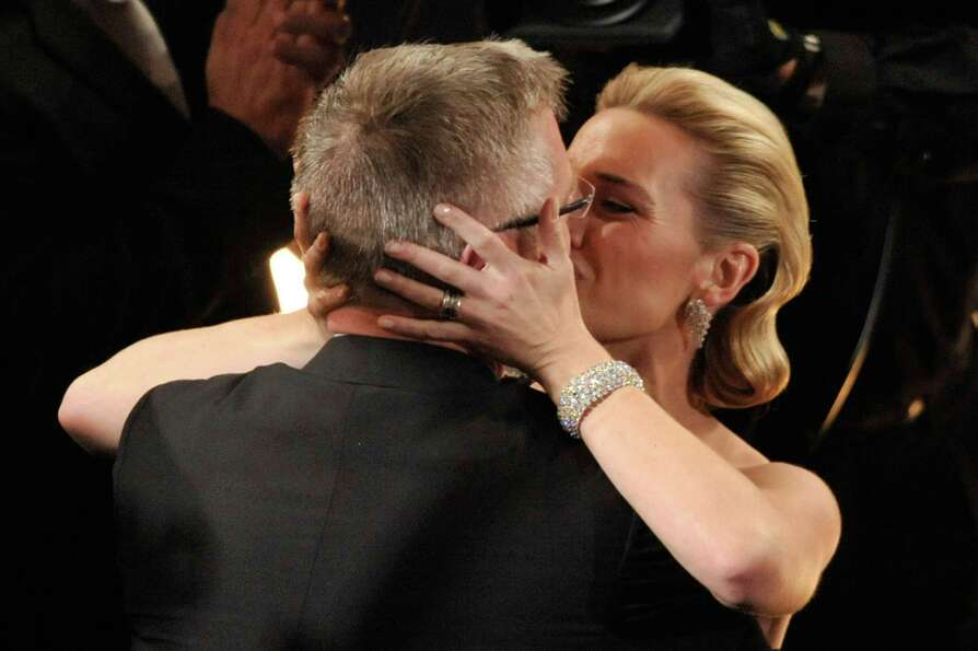 Actress Kate Winslet kisses her husband, director Sam Mendes, as she wins the Best Actress award for