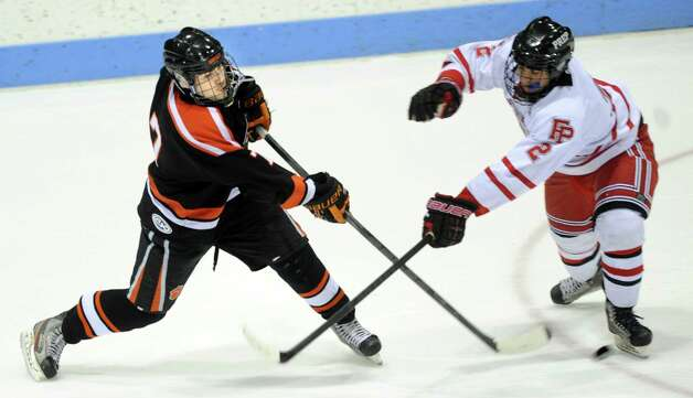 Ridgefield's Christopher Morrow passes the puck as Fairfield Prep's Andrew Hatton defends during the boys hockey State Tournament Class I Semifinals Wednesday, Mar. 13, 2013 at Ingalls Rink in New Haven, Conn. Photo: Autumn Driscoll / Connecticut Post