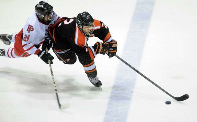 Ridgefield's Vincent Rella controls the puck as Fairfield Prep's Matt McKinney defends during the boys hockey State Tournament Class I Semifinals Wednesday, Mar. 13, 2013 at Ingalls Rink in New Haven, Conn. Photo: Autumn Driscoll / Connecticut Post