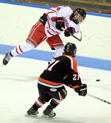 Fairfield Prep's Brendan Killoy passes the puck as Ridgefield's Cameron McGuire defends during the boys hockey State Tournament Class I Semifinals Wednesday, Mar. 13, 2013 at Ingalls Rink in New Haven, Conn. Photo: Autumn Driscoll / Connecticut Post