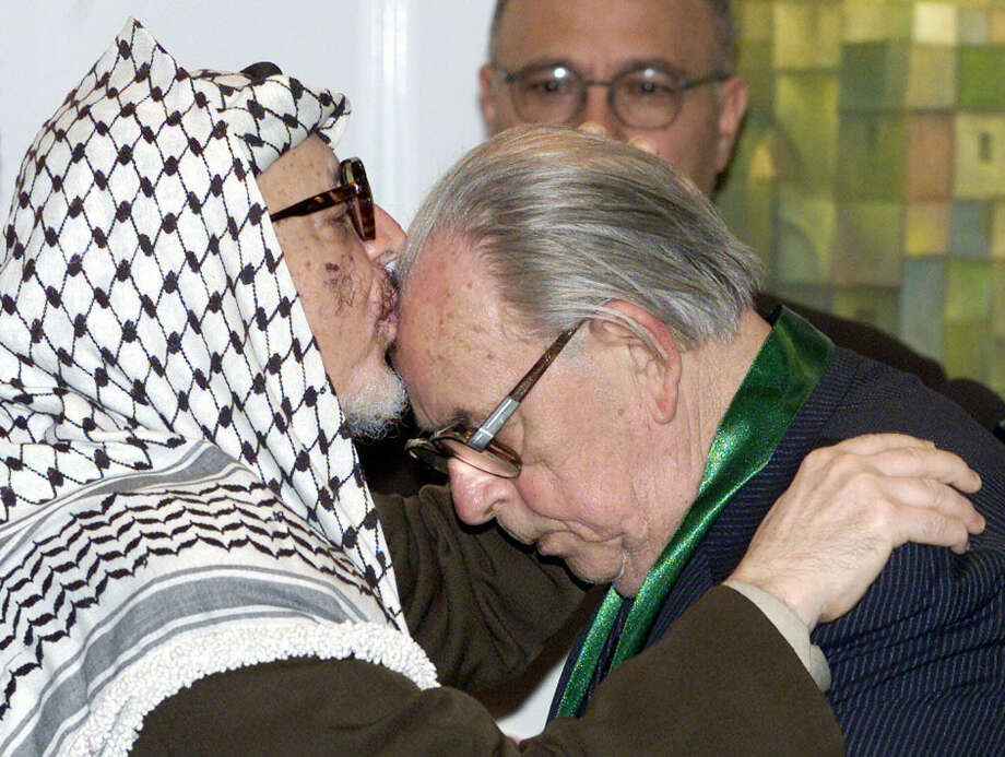 "Palestinian Yasser Arafat dominated the news and then he died. Here he is kissing Hans-Juergen Wischnewski, a former Social Democrats (SPD) politician and Middle East expert, after decorating him with the ""Bethlehem 2000"" order during a ceremony. Photo: ANDREAS ALTWEIN, Getty / 2005 AFP"