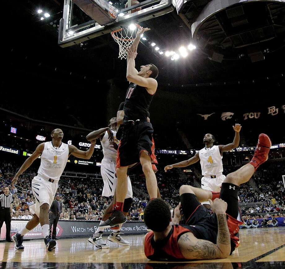 Texas Tech forward Dejan Kravic (11) tips in the game-winning basket in an NCAA college basketball game against West Virginia in the Big 12 men's tournament Wednesday, March 13, 2013, in Kansas City, Mo. Texas Tech won 71-69. (AP Photo/Charlie Riedel) Photo: Charlie Riedel, Associated Press / AP