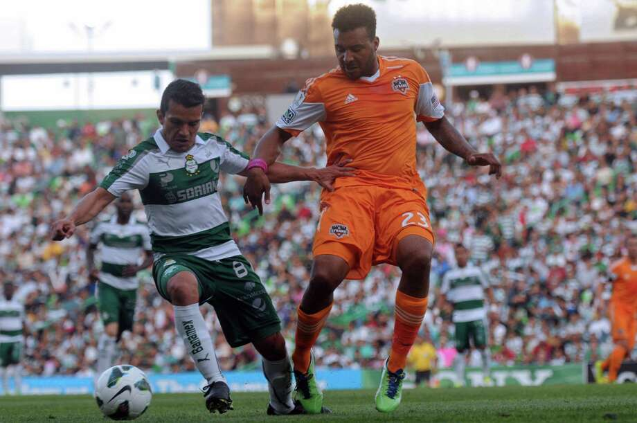 Juan Pablo Rodriguez of Santos vies for the ball with Giles Barnes of the Dynamo. Photo: LUIS FUENTES, AFP/Getty Images / AFP