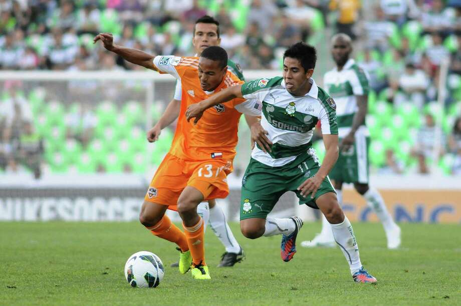 Ricardo Clark of the Dynamo vies for the ball with Nestor Calderon of Santos Laguna. Photo: ANDRES HERRERA, AFP/Getty Images / AFP