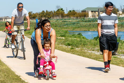 Two-year-old Hailey gets a bit of tricycle assistance from mom Cassandra Ramos as folks enjoy a leisurely day at Padre County Park.