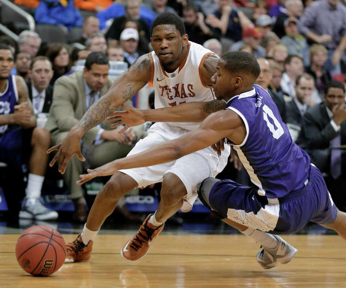 TCU guard Charles Hill Jr. (0) tries to steal the ball away from Texas guard Julien Lewis during the first half an NCAA college basketball game in the Big 12 men's tournament Wednesday, March 13, 2013, in Kansas City, Mo. (AP Photo/Charlie Riedel)