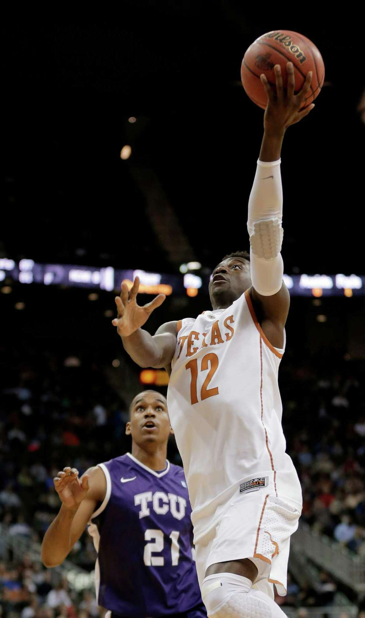 Texas guard Myck Kabongo (12) gets past TCU guard Nate Butler Lind (21) to put up a shot during the first half an NCAA college basketball game in the Big 12 men's tournament Wednesday, March 13, 2013, in Kansas City, Mo. (AP Photo/Charlie Riedel)