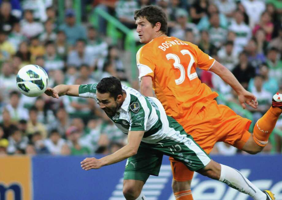 Bobby Boswell (R) of Houston's Dynamo vies for the ball with Herculez Gomez of Mexican Santos during their CONCACAF Champions League football match on March 13, 2013 in Torreon, Mexico. Santos won by 3-0. AFP PHOTO/ANDRES HERRERAANDRES HERRERA/AFP/Getty Images Photo: ANDRES HERRERA, AFP/Getty Images / AFP