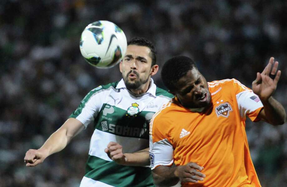 Kofi Sarkodie (R) of Houston's Dynamo jumps for the ball with Herculez Gomez of Mexican Santos during their CONCACAF Champions League football match on March 13, 2013 in Torreon, Mexico. Santos won by 3-0. AFP PHOTO/ANDRES HERRERAANDRES HERRERA/AFP/Getty Images Photo: ANDRES HERRERA, AFP/Getty Images / AFP