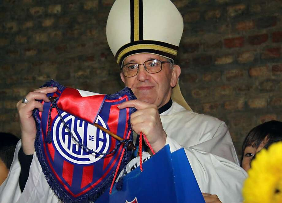 Undated file photo of Argentina's cardinal Jorge Mario Bergoglio posing with the emblem of San Lorenzo's football team, which he supports in Buenos Aires. Bergoglio has been elected Pope on March 13, 2013, to replace the frail Benedict XVI as leader of the world's 1.2 billon Catholics. Photo: --, AFP/Getty Images