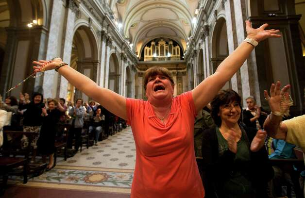 Paola La Rocca celebrates after hearing on the speakers at the Metropolitan Cathedral that Buenos Aires' Archbishop Jorge Bergoglio was chosen as Pope in Buenos Aires, Argentina, Wednesday, March 13, 2013. Bergoglio is the first pope ever from the Americas and the first from outside Europe in more than a millennium. (AP Photo/Victor R. Caivano) Photo: Victor R. Caivano