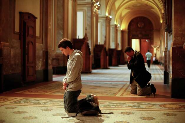 People pray inside the Metropolitan Cathedral in Buenos Aires, Argentina,  Wednesday, March 13, 2013.  White smoke billowed from the chimney of the Sistine Chapel, Wednesday evening, in Vatican City, meaning 115 cardinals in a papal conclave elected a new leader for the world's 1.2 billion Catholics. (AP Photo/Victor R. Caivano) Photo: Victor R. Caivano