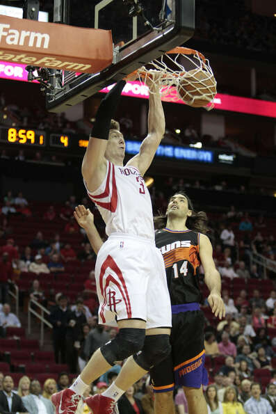 Rockets center Omer Asik dunks on Luis Scola of the Suns.