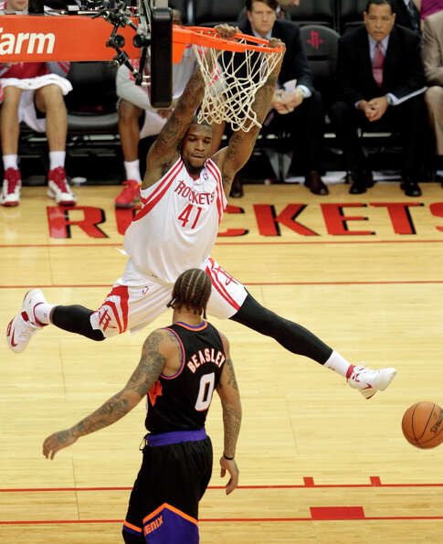 Thomas Robinson of the Rockets throws down a dunk against Micheal Beasley of the Suns.