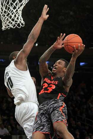 Cincinnati's Sean Kilpatrick (23) goes up against Providence's Kadeem Batts during the second half of an NCAA college basketball game at the Big East Conference tournament, Wednesday, March 13, 2013 in New York. Cincinnati won 61-44. (AP Photo/Mary Altaffer) Photo: Mary Altaffer