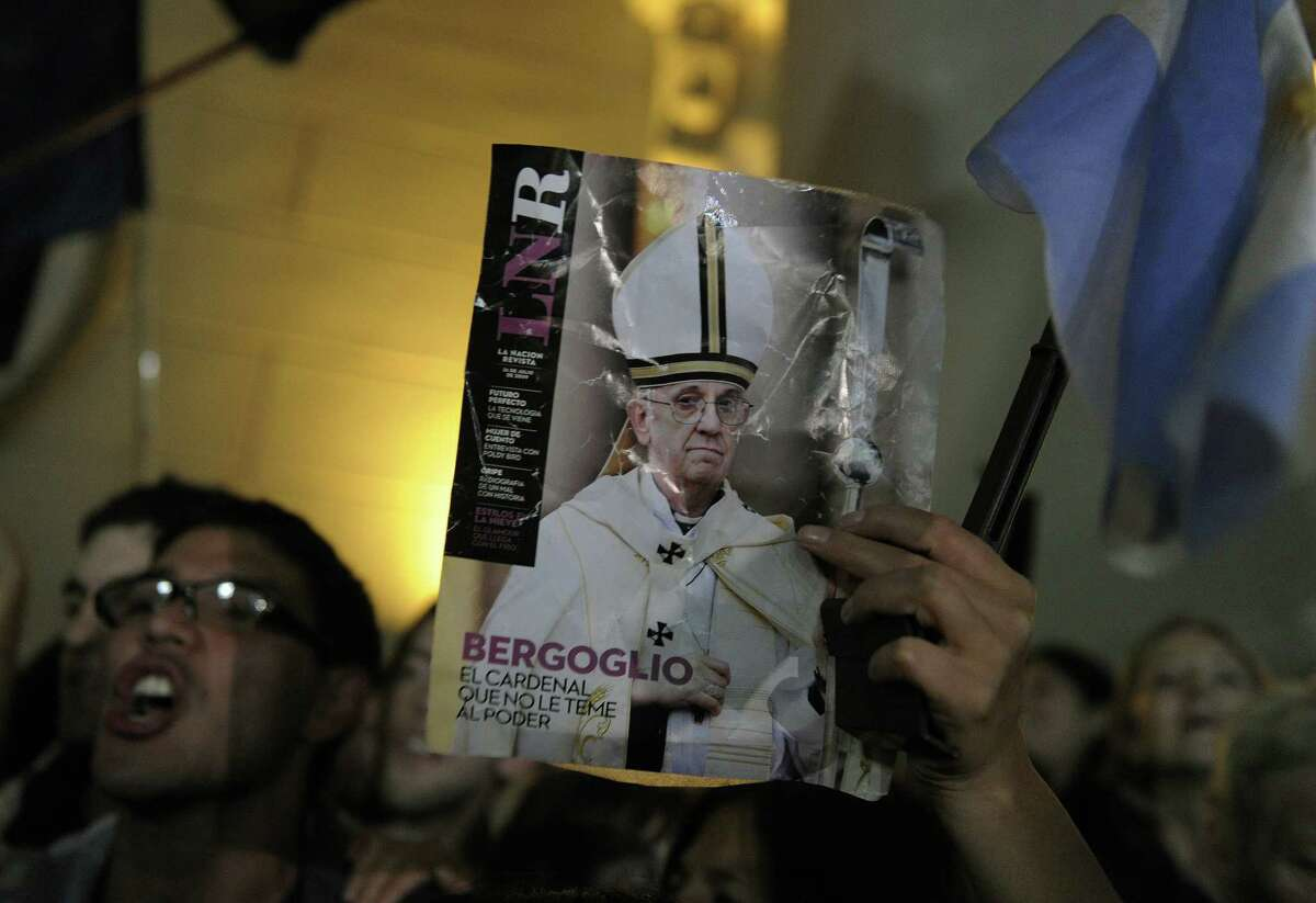 A woman holds a picture at the Metropolitan Cathedral in Buenos Aires, Argentina, of Cardinal Jorge Bergoglio after he was selected as the new pope.