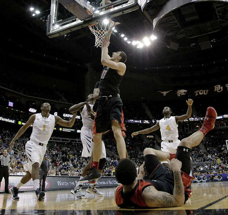Texas Tech forward Dejan Kravic cleans up Jamal Williams' missed 3-pointer in the final second to give the Red Raiders a victory over West Virginia at the Big 12 tournament. Photo: Charlie Riedel / Associated Press