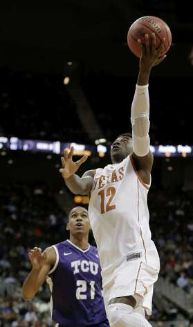 Texas guard Myck Kabongo, who had 16 points and seven assists, lays the ball up over TCU guard Nate Butler Lind in Kansas City, Mo. Photo: Charlie Riedel / Associated Press