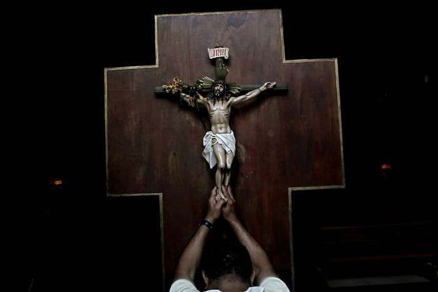A man prays as he touches a crucifix at La Candelaria church in Caracas, Venezuela, Wednesday, March 13, 2013. Latin Americans reacted with joy on Wednesday at news that Argentine Cardinal Jorge Bergoglio has become the first pope ever from the Americas and the first from outside Europe in more than a millennium. (AP Photo/Rodrigo Abd) Photo: Rodrigo Abd, Associated Press