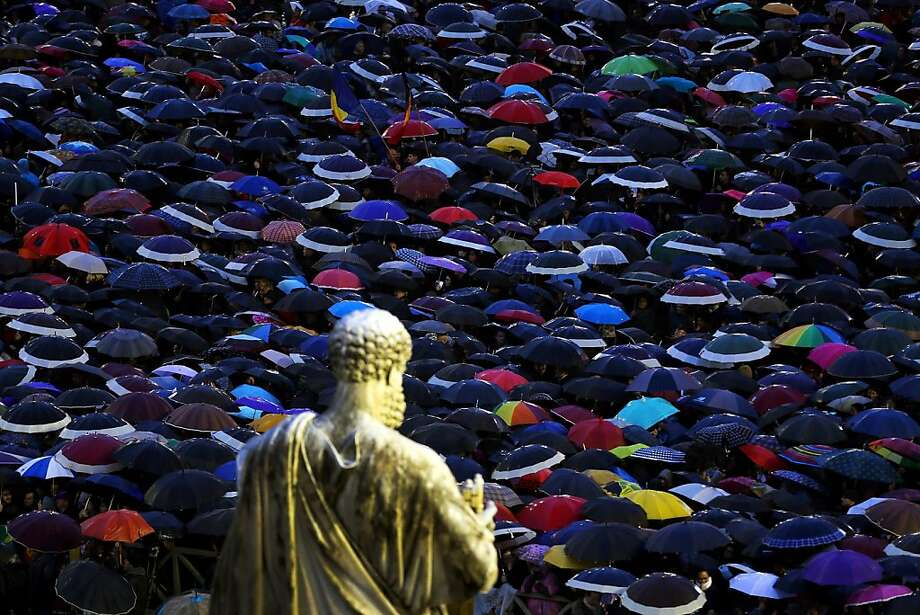 VATICAN CITY, VATICAN - MARCH 13:  A statue of St Peter looks down upon people sheltering from the rain under umbrellas as they gather in St Peter's Square as they wait for news on the election of a new Pope on March 13, 2013 in Vatican City, Vatican. Pope Benedict XVI's successor is being chosen by the College of Cardinals in Conclave in the Sistine Chapel. The 115 cardinal-electors, meeting in strict secrecy, will need to reach a two-thirds-plus-one vote majority to elect the 266th Pontiff.  (Photo by Joe Raedle/Getty Images)  *** BESTPIX *** Photo: Joe Raedle, Getty Images