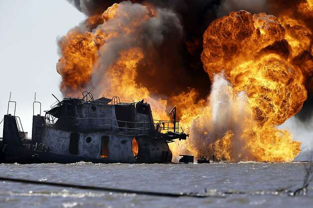 A fire still burns Wednesday, March 13, 2013, after a tugboat and barge hit a gas pipeline Tuesday evening in Perot Bay in Lafourche Parish, La., about 30 miles south of New Orleans. Coast Guard Cmdr. Russ Bowen said it appears the barge is intact and none of its cargo of crude oil was leaking, though there were patches of oily sheen in the area. The Coast Guard was investigating whether those sheens were related to the accident. (AP Photo/Gerald Herbert) Photo: Gerald Herbert, Associated Press