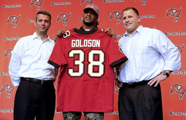 Dashon Goldson displays his new uniform, flanked by general manager Matt Dominik and coach Greg Schiano. Goldson's deal is reportedly for $41.25 million over five years. Photo: Chris Urso, Associated Press