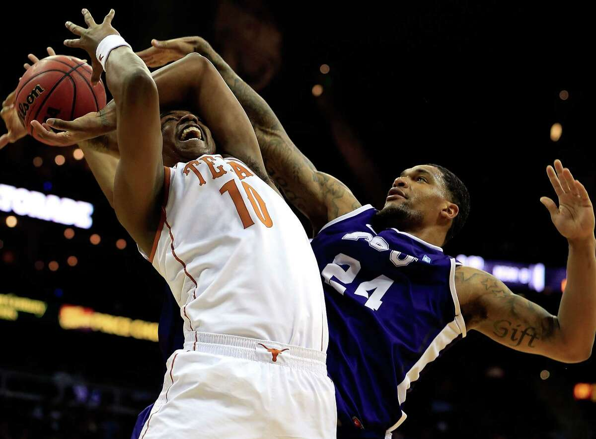 KANSAS CITY, MO - MARCH 13: Jonathan Holmes #10 of the Texas Longhorns is fouled by Adrick McKinney #24 of the TCU Horned Frogs during the first round of the 2013 Big 12 Men's Basketball Championship at Sprint Center on March 13, 2013 in Kansas City, Missouri.