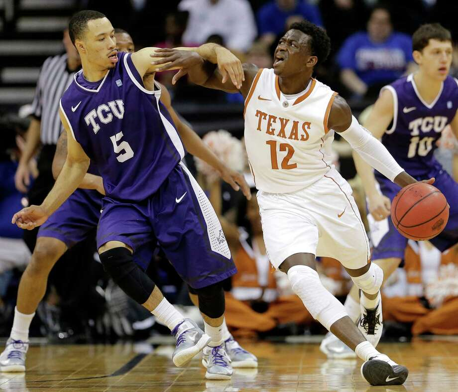 Texas guard Myck Kabongo (12) is pressured by TCU guard Kyan Anderson (5) as he drives during the second half of an NCAA college basketball game in the Big 12 tournament, Wednesday, March 13, 2013, in Kansas City, Mo. Texas won 70-57. (AP Photo/Charlie Riedel) Photo: Charlie Riedel, Associated Press / AP
