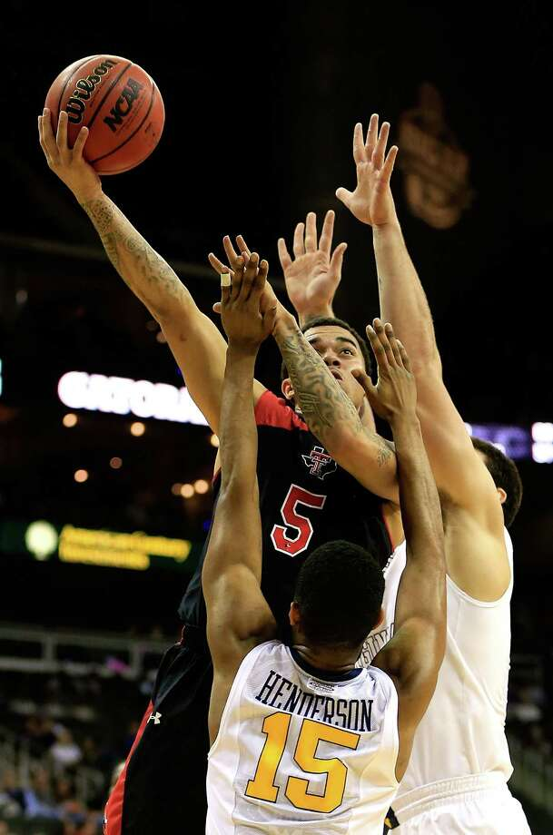 KANSAS CITY, MO - MARCH 13:  Josh Gray #5 of the Texas Tech Red Raiders shoots over Terry Henderson #15 of the West Virginia Mountaineers during the first round of the 2013 Big 12 Men's Basketball Championship at Sprint Center on March 13, 2013 in Kansas City, Missouri. Photo: Jamie Squire, Getty Images / 2013 Getty Images