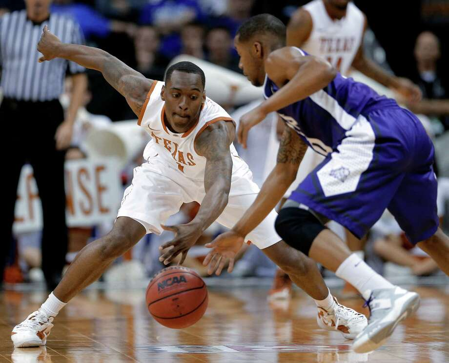 Texas guard Sheldon McClellan (1) tries to steal the ball from TCU guard Charles Hill Jr., right, during the first half an NCAA college basketball game in the Big 12 men's tournament Wednesday, March 13, 2013, in Kansas City, Mo. (AP Photo/Charlie Riedel) Photo: Charlie Riedel, Associated Press / AP