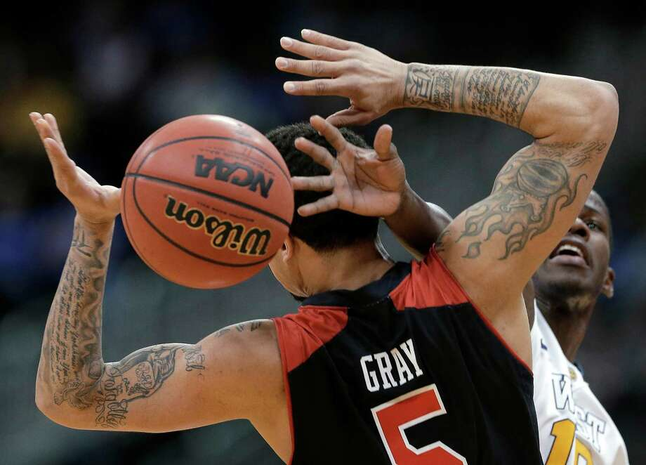 West Virginia guard Eron Harris (10) knocks the ball away from Texas Tech guard Josh Gray (5) during the first half an NCAA college basketball game in the Big 12 men's tournament Wednesday, March 13, 2013, in Kansas City, Mo. (AP Photo/Charlie Riedel) Photo: Charlie Riedel, Associated Press / AP