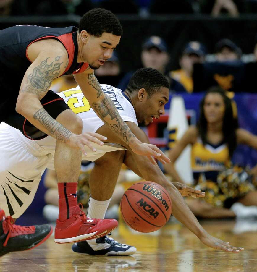Texas Tech guard Josh Gray, left, and West Virginia guard Terry Henderson (15) chase a loose ball during the first half an NCAA college basketball game in the Big 12 men's tournament Wednesday, March 13, 2013, in Kansas City, Mo. (AP Photo/Charlie Riedel) Photo: Charlie Riedel, Associated Press / AP
