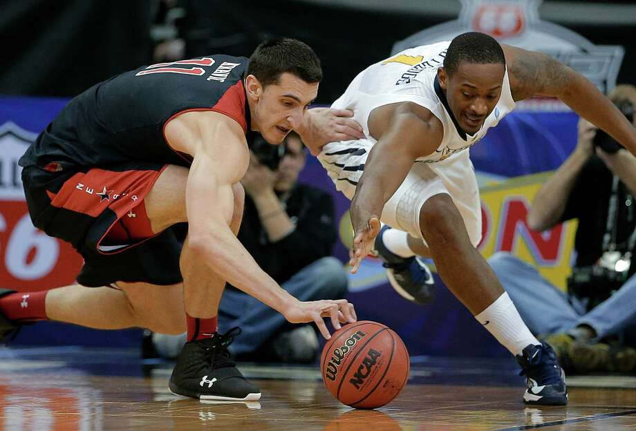 Texas Tech forward Dejan Kravic (11) and West Virginia forward Dominique Rutledge (1) chase a loose ball during the first half an NCAA college basketball game in the Big 12 men's tournament Wednesday, March 13, 2013, in Kansas City, Mo. (AP Photo/Charlie Riedel) Photo: Charlie Riedel, Associated Press / AP