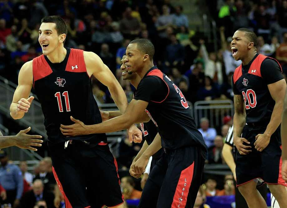 KANSAS CITY, MO - MARCH 13:  Dejan Kravic #11 of the Texas Tech Red Raiders celebrates with Jordan Tolbert #32, Jamal Williams, Jr. #23, and Jaye Crockett #30 as the Red Raiders defeat the West Virginia Mountaineers 71-69 to win their first round game of the 2013 Big 12 Men's Basketball Championship at Sprint Center on March 13, 2013 in Kansas City, Missouri. Photo: Jamie Squire, Getty Images / 2013 Getty Images