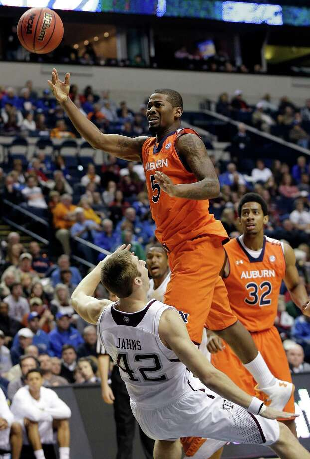 Auburn forward Shaquille Johnson (5) shoots as Texas A&M forward Jarod Jahns (42) falls to the court during the first half of an NCAA college basketball game at the Southeastern Conference tournament in Nashville, Tenn., Wednesday, March 13, 2013. (AP Photo/Dave Martin) Photo: Dave Martin, Associated Press / AP