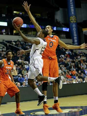 Texas A&M guard Fabyon Harris (12) heads to the hoop as Auburn center Asauhn Dixon-Tatum (0) defends during the second half of an NCAA college basketball game at the Southeastern Conference tournament, Wednesday, March 13, 2013, in Nashville, Tenn. (AP Photo/Dave Martin) Photo: Dave Martin, Associated Press / AP