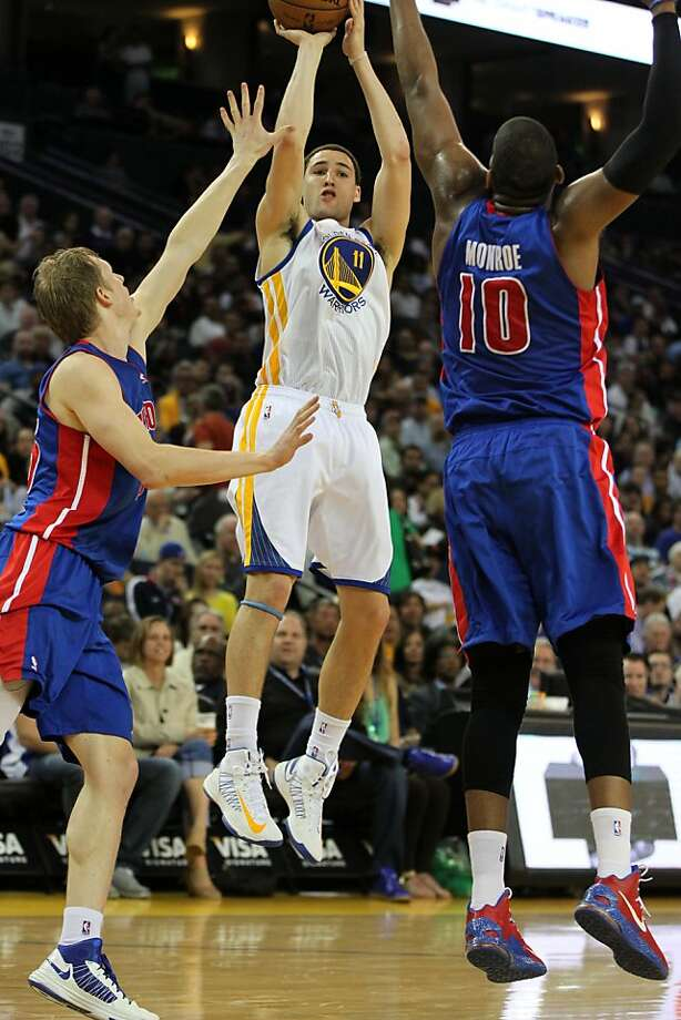 Golden State Warriors guard Klay Thompson (11) shoots between two Detroit Pistons defenders in the first half of their NBA basketball game Wednesday, March 13, 2013, in Oakland Calif. Photo: Lance Iversen, The Chronicle