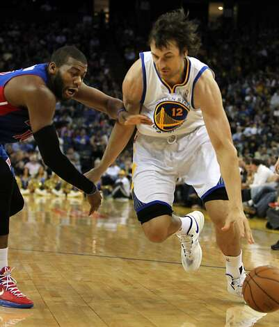 Golden State Warriors center Andrew Bogut (12) drives past Detroit Pistons defenders in the first half of their NBA basketball game Wednesday, March 13, 2013, in Oakland Calif. Photo: Lance Iversen, The Chronicle