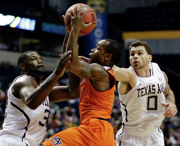 Auburn guard Josh Wallace (11) drives to the basket against Texas A&M forwards Kourtney Roberson (32) and Andrew Young (0) during the first half of an NCAA college basketball game at the Southeastern Conference tournament, Wednesday, March 13, 2013, in Nashville. (AP Photo/Dave Martin) Photo: Dave Martin, Associated Press / AP