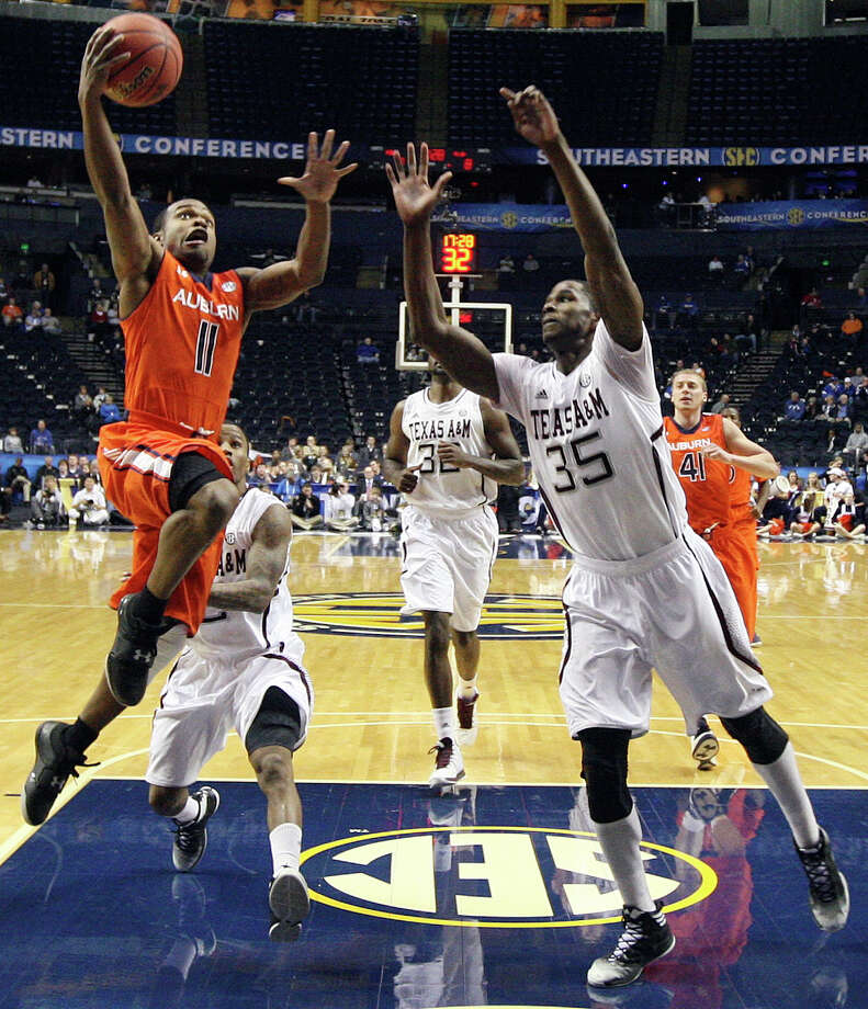 Auburn guard Josh Wallace (11) heads to the basket as Texas A&M forward Ray Turner (35) defends during the first half of an NCAA college basketball game at the Southeastern Conference tournament, Wednesday, March 13, 2013, in Nashville. (AP Photo/Dave Martin) Photo: =snum=, Associated Press / AP